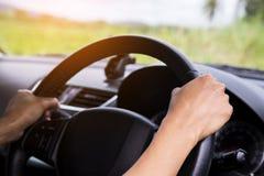 司机在方向盘的` s手在有美好的绿色森林透视的一辆汽车里面 免版税图库摄影