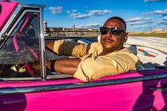 司机在经典美国桃红色雪佛兰中坐 免版税库存图片