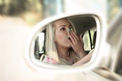 司机女孩哈欠,当驾驶汽车时 免版税库存照片