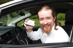 司机微笑的坐在有驾驶执照的汽车 免版税库存图片