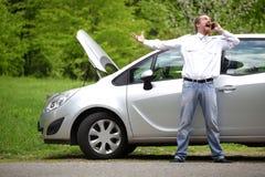 司机愤怒一辆残破的汽车由路 库存图片