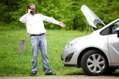 司机愤怒与手机一辆残破的汽车 库存照片
