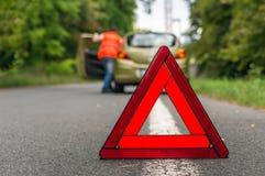 司机推挤残破的汽车和红色警告三角 库存照片