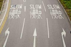 司机的双语(英语和汉语)缓慢的路标 库存照片