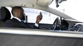 司机等待的上司,乏味移动在他的智能手机的新闻应用 免版税库存图片