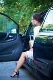 司机` s位子的体贴的女孩与开放的门 库存照片