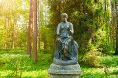 司音乐及抒情诗的女神铜雕塑-音乐和雄辩冥想,与一个纸卷在她的手上 Pavlovsk,圣彼德堡,俄罗斯 库存照片