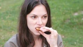 吃一个三明治用面包和香肠的一名无家可归的妇女的画象 股票视频