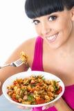 吃一个五颜六色的素食面团的愉快的健康少妇 免版税库存图片