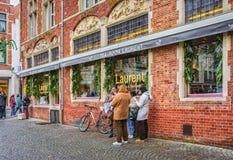 吃一个便餐的未知的人民在Sint-Salvatorskerkhof的茶室劳伦特附近 比利时布鲁日 免版税库存图片