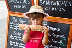 吃一个大三明治的女孩 免版税库存图片
