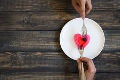 吃一个心形的蛋糕的夫妇 免版税库存照片