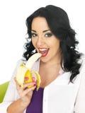 吃一个成熟香蕉的健康可爱的少妇 库存照片