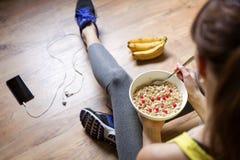 吃一个燕麦粥用莓果的女孩在锻炼以后 fitne 免版税库存图片