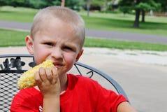 吃一个玉米穗的逗人喜爱的年轻小孩男孩 免版税库存图片