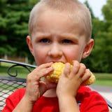 吃一个玉米穗的逗人喜爱的年轻小孩男孩 免版税库存照片
