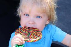 吃一个美味的五颜六色的棒棒糖的小孩 有漩涡棒棒糖的男婴 库存图片
