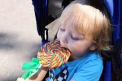 吃一个美味的五颜六色的棒棒糖的小孩 有漩涡棒棒糖的男婴 库存照片