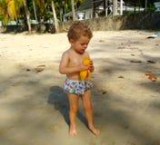 吃一个芒果的男孩在热带 免版税库存图片