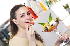 吃一个草莓和冰淇凌点心在酒吧的妇女 图库摄影