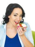 吃一个薄脆饼干用无盐干酪乳酪和新鲜的蕃茄的年轻健康妇女 免版税库存照片