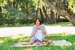 吃一个西瓜的微笑的愉快的妇女在公园 免版税图库摄影