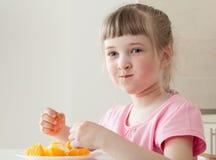 吃一个鲜美桔子的愉快的小女孩 图库摄影