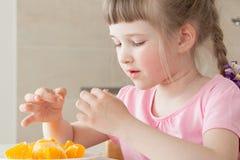 吃一个鲜美桔子的愉快的小女孩 免版税库存图片