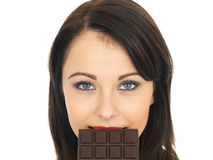 吃一个黑暗的巧克力块的少妇 免版税库存照片