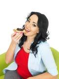 吃一个整粒薄脆饼干用乳酪和腌汁的年轻愉快的妇女 免版税库存图片