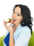 吃一个整粒薄脆饼干用无盐干酪乳酪和新鲜的成熟蕃茄的年轻健康妇女 免版税库存照片