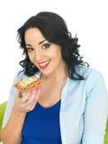 吃一个整粒薄脆饼干用花生酱和切的香蕉的少妇 免版税图库摄影