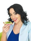 吃一个整粒薄脆饼干用酸奶干酪和鲕梨的少妇 图库摄影