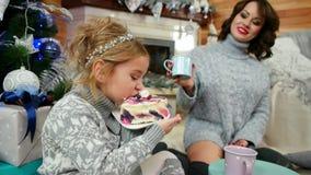 吃一块大蛋糕在圣诞树,妈妈和女儿,由壁炉的家庭的女孩吃一个点心与 股票录像