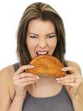 吃一块被烘烤的康瓦尔郡菜肉烘饼的可爱的少妇 图库摄影