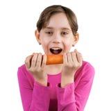 吃一棵大红萝卜的愉快的女孩 免版税图库摄影