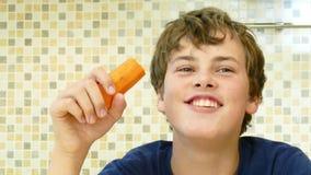 吃一棵红萝卜高兴地的年轻男孩 免版税库存图片