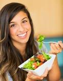 吃一碗健康有机沙拉的美丽的少妇 免版税图库摄影