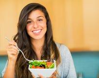 吃一碗健康有机沙拉的美丽的少妇 库存图片