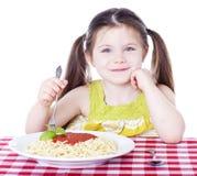 吃一碗意大利面食的美丽的女孩用调味汁 免版税图库摄影