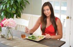 吃一顿新作膳食的美丽的少妇 库存照片