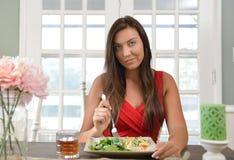吃一顿新作膳食的美丽的少妇 免版税库存照片