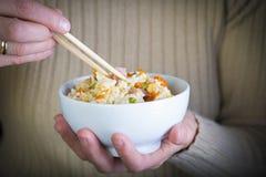 吃三双欢欣米witn筷子的妇女 免版税库存照片
