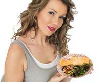 吃三文鱼和豆沙拉的年轻可爱的妇女 免版税库存照片