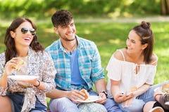 吃三明治的愉快的朋友在夏天野餐 免版税图库摄影