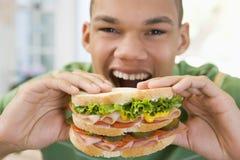 吃三明治的男孩少年 免版税库存图片