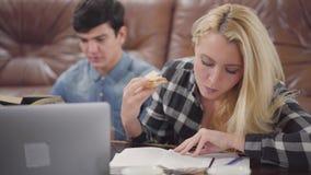 吃三明治的画象逗人喜爱的白肤金发的年轻女人读书笔记本,当她的关于时的男朋友探索的信息 股票视频