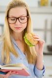 吃三明治和阅读书的少妇 免版税库存图片