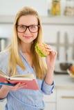 吃三明治和阅读书的愉快的女孩 免版税库存照片