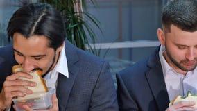 吃三明治的两个商人在午餐在办公室 免版税库存照片